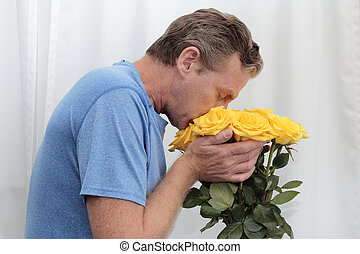 Male Smelling and Holding Yellow Bouquet of Roses