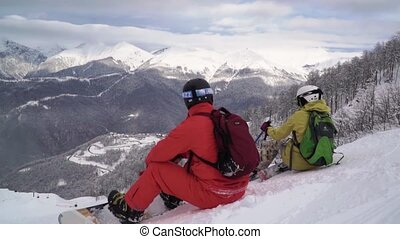 Male snowboarder and female skier are sitting on the hill and resting during a break. Skiers enjoy XXX snow mountain peak in front of them.
