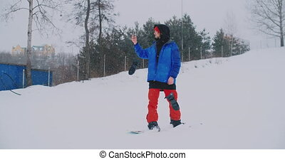 Male snowboarder in a blue jacket is live broadcast from...