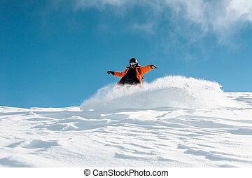 Male snowboarder in bright orange sportswear riding down the powder snow hill