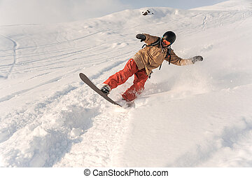 Male snowboarder in sportswear and helmet riding down the powder snow hill