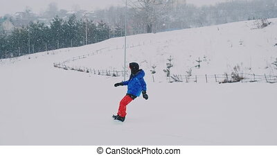 Male snowboarder rides on a Board in the snow from the ski...