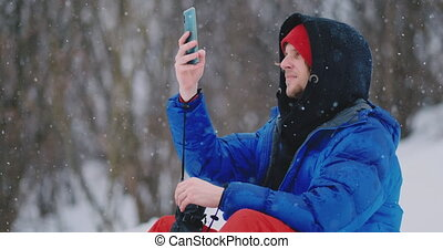 Male snowboarder sitting on the snow taking photos on the...
