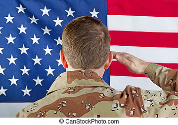 Male soldier saluting large USA Flag while indoors