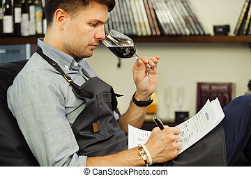 Male sommelier tasting red wine and making notes. Profession...