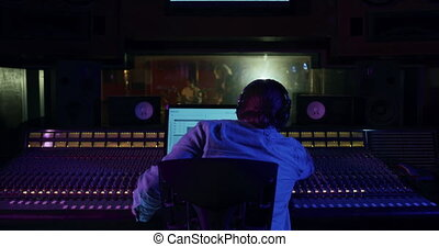 Male sound engineer working at a mixing desk - Rear view of ...