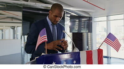 Side view close up of a serious young African American man standing at a lectern decorated with a US flags addressing the audience at a political rally