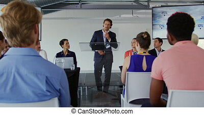 Male speaker addressing the audience at a business ...