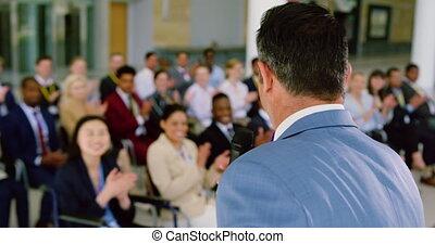 Side view of Caucasian male speaker speaks in a business seminar. Business people applauding him in a seminar 4k