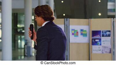 male speaker speaks in a business seminar at modern office ...