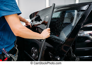 Male specialist applying car tinting film, installation process, tinted auto glass installing procedure