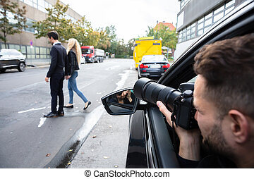 Male Spy Taking Photograph Of A Couple Walking On Street