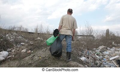 Male standing on the hill at garbage dump site