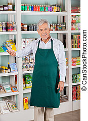 Male Store Owner Gesturing In Supermarket - Happy senior...