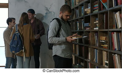 Male student choosing book on shelf in library
