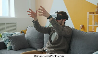 Male student in casual clothing is enjoying augmented reality glasses gesturing wearing headset at home sitting on couch alone. People and fun concept.