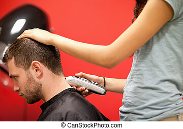 Male student having a haircut with a hair clippers