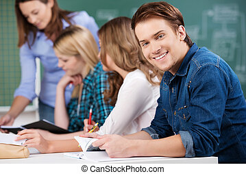 Male Student Holding Book With Classmates And Teacher At Desk