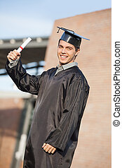 Male Student Holding Diploma On Graduation Day At Campus -...