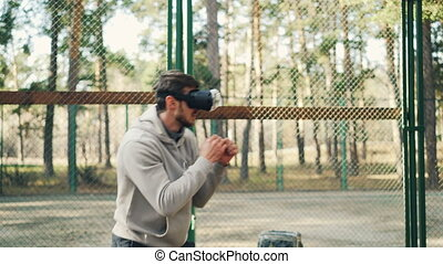 Male student is training in park wearing virtual reality...
