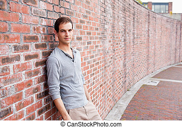 Male student leaning on a wall
