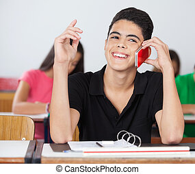 Male Student Looking Away While Talking On Phone