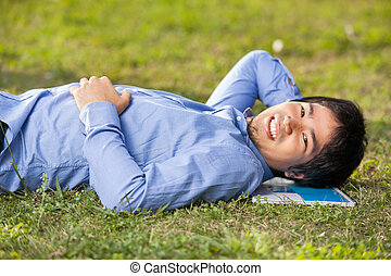 Male Student Lying On Grass At College Campus