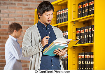 Male Student Reading Book In College Library
