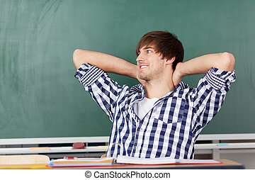 Male Student Relaxing At Desk Against Chalkboard