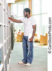Male Student Selecting Book In Bookstore
