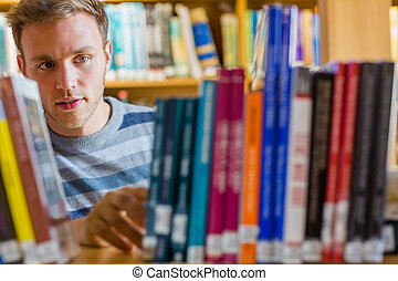 Male student selecting book in the library