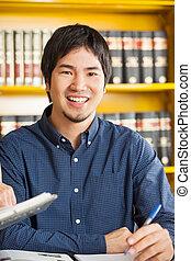 Male Student Sitting Against Bookshelf In University Library