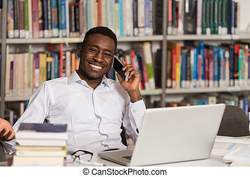 Male Student Talking On The Phone In Library