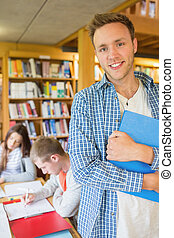 Male student with others in background at library