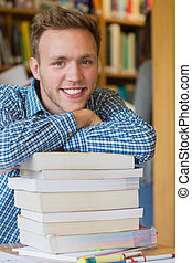Male student with stack of books at library