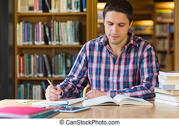 Male student writing notes at desk in the library