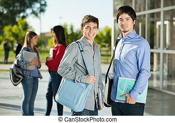Male Students With Friends Standing In Background On Campus