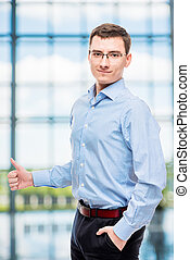 Male successful young businessman posing in office