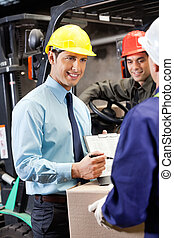 Male Supervisor Showing Clipboard To Foreman