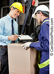 Male Supervisor Showing Clipboard To Foreman - Young male...