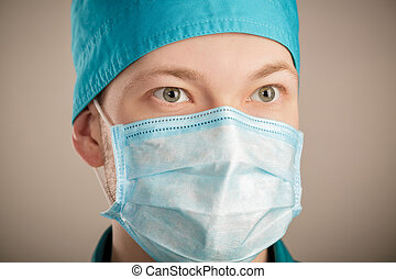 male surgeon in mask looking at camera on grey background, close up