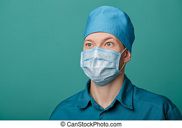 male surgeon in mask on blue background, close up