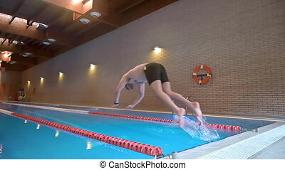 Male swimmer jumping into swimming pool in slow motion. High quality FullHD footage