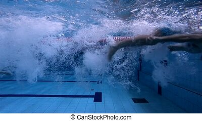 Male swimmer swims freestyle and turn around under water