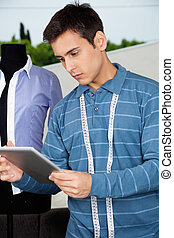 Male Tailor Holding Tablet PC - Young male tailor in casual ...