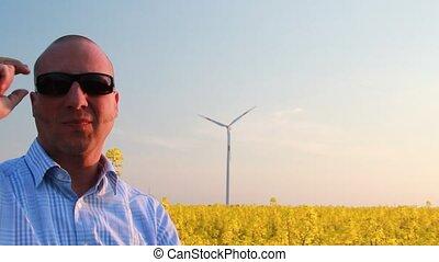 Male - taking off sun glasses beneath rape field and wind...