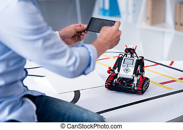 Male taking pictures of a droid with  mobile phone