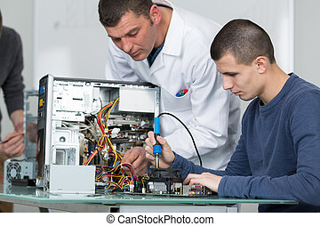 male teacher assisting a young man in fixing computer