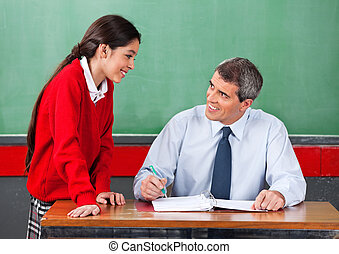 Male Teacher Discussing With Schoolgirl At Desk