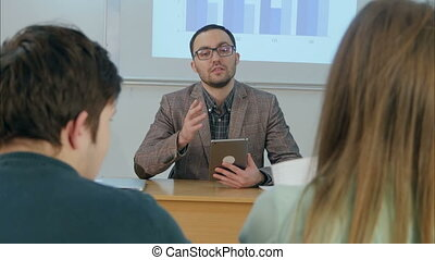 Male teacher holding a tablet sitting in front of class
